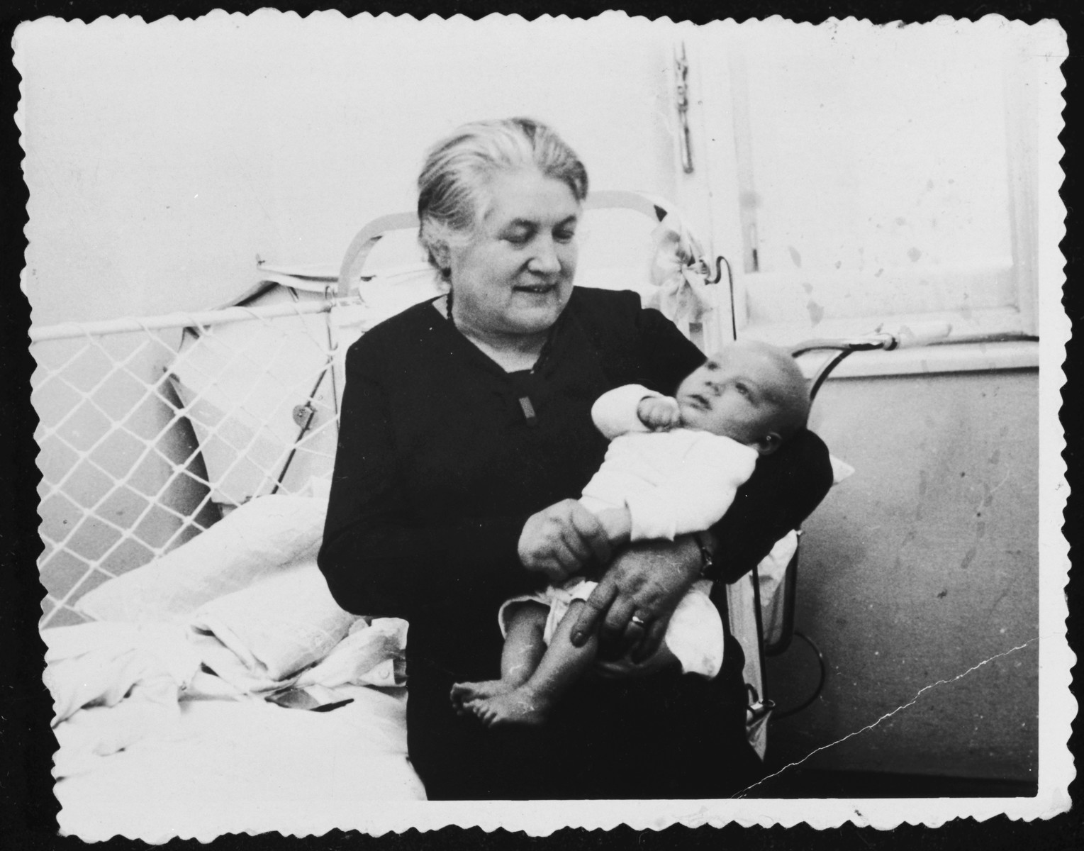 A Jewish grandmother cradles her infant grandchild.  Pictured are the grandmother and cousin of Rita Blattberg Blumstein, Mrs.Schreiber and Romek.