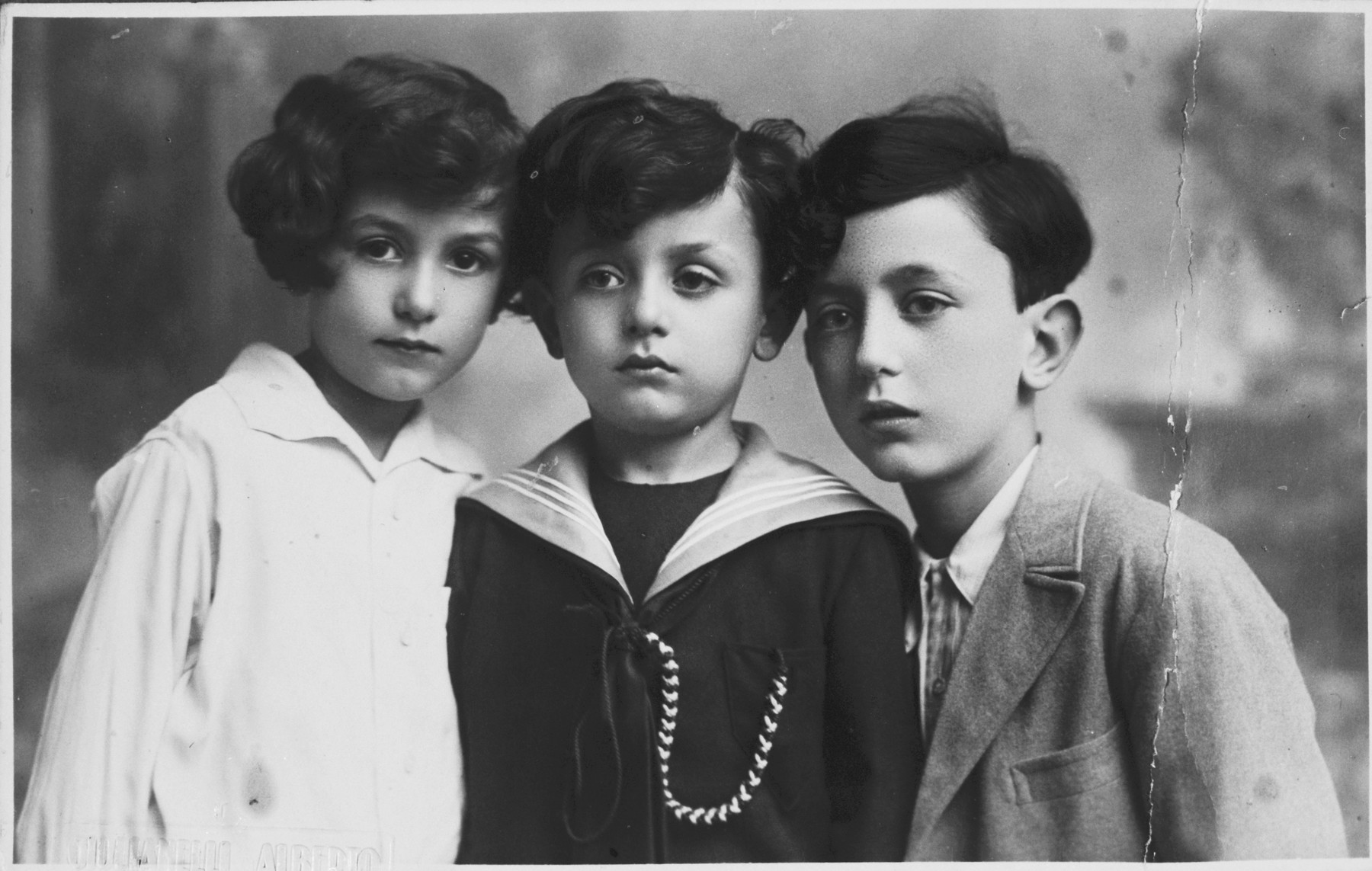 Studio portrait of three Italian-Jewish siblings, the children of Leo Minerbi.  Pictured are cousins of Sergio Minerbi, (from left) Luisa, Giorgio-Lot, and Ruggero.