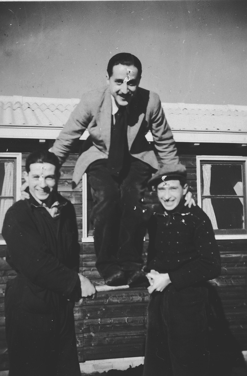Three Jewish men pose in a human pyramid outside one of the barracks in the Westerbork internment camp.