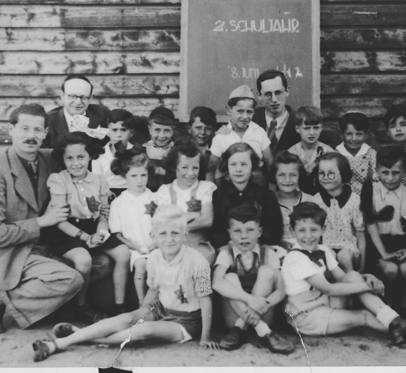 Group portrait of Jewish school children and their teachers, all of whom are wearing Jewish stars, in the Westerbork transit camp.  Among those pictured is Michael Fink (back row center with the white shirt and hat).