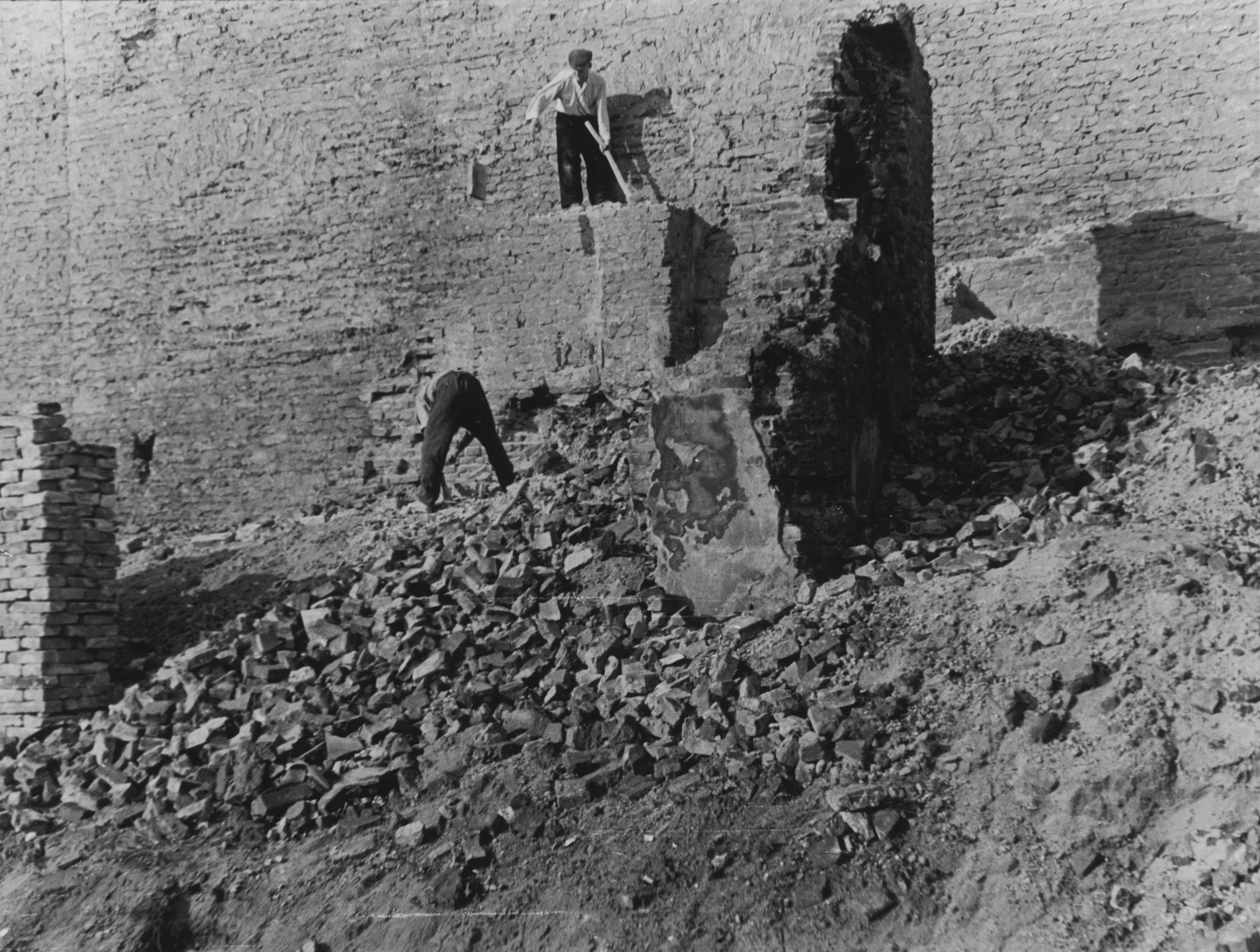 Polish workmen dismantle the wall of the Warsaw ghetto a few months after its destruction.