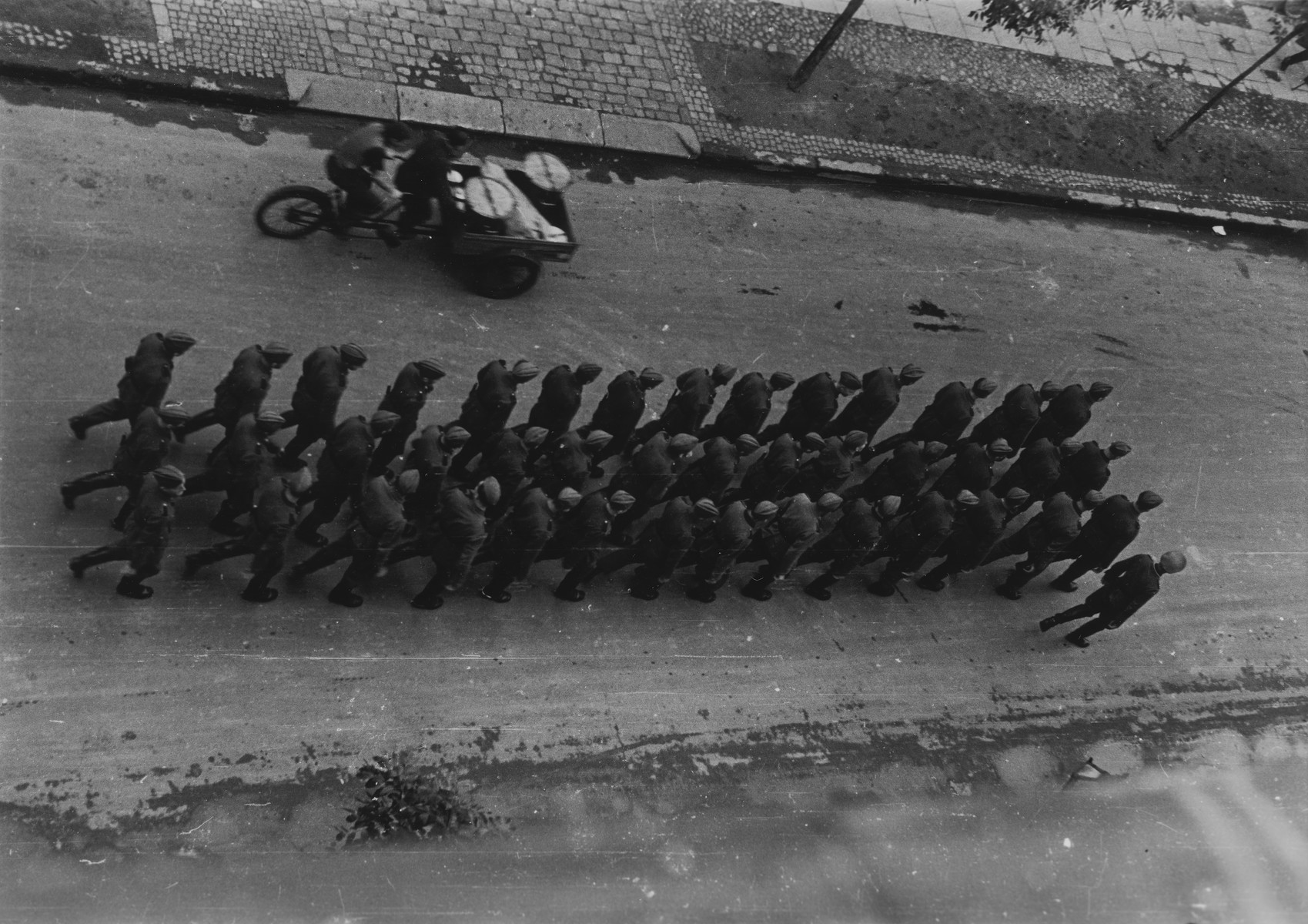 Aerial view of a column of German troops marching down Sienna Street shortly after the destruction of the Warsaw ghetto.