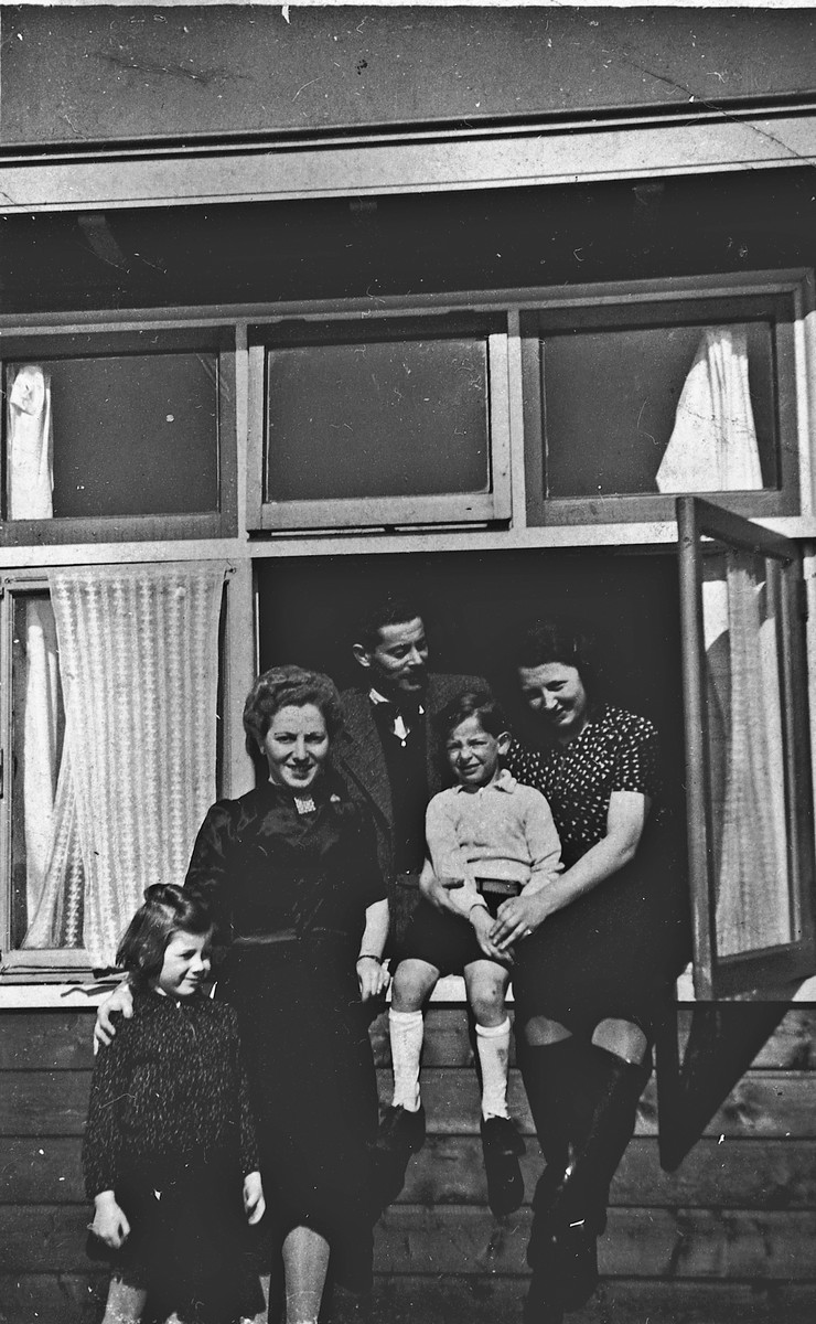 German-Jewish refugees pose in and near the window of one of the barracks of the Westerbork camp.  Among those pictured are Herta Fink and her son Michael, far right.