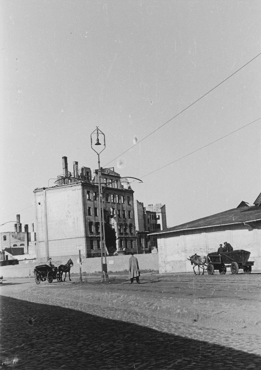 Horse and carriages ride down Okopowa Street in front of the destroyed Warsaw ghetto.