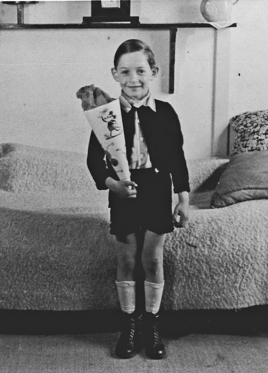 A German-Jewish refugee child poses with a cone filled with treats on his first day of school in the Westerbork internment camp.  Pictured is Michael Fink.
