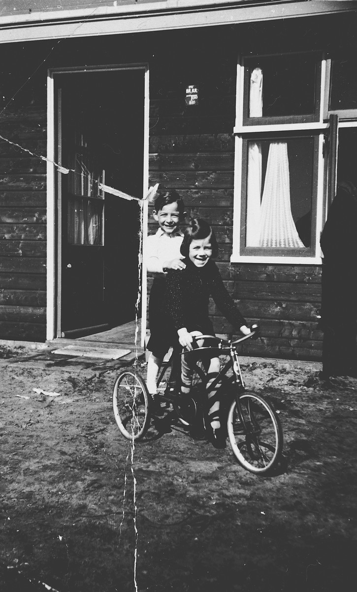 Two Jewish children share a bicycle outside one of the barracks in the Westerbork internment camp.  Pictured on the left is Michael Fink.