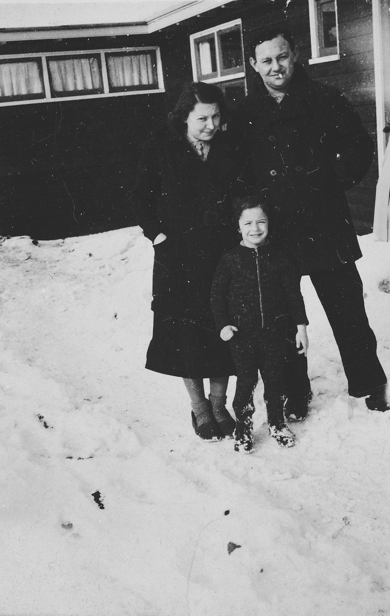 A German-Jewish family poses in the snow outside one of the barracks of the Westerbork camp.  Pictured are Herta and Manfred Fink and their son Michael.