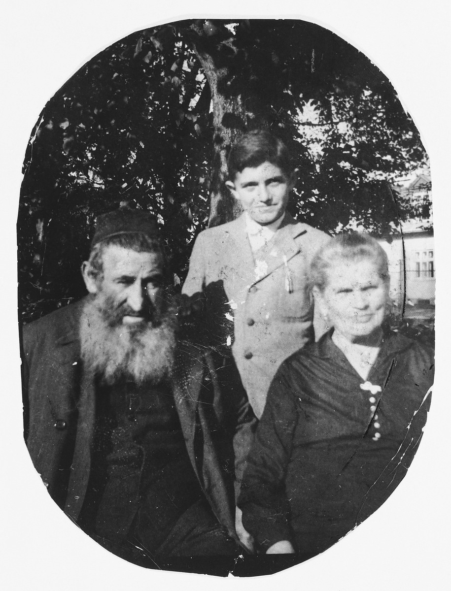 Portrait of a Jewish child in Drohobycz with his great-grandparents.  Pictured are Paul Lustig (center) and Salomon and Gitel Erdman.  Gitel was the midwife for much of the Drohobycz community, and her husband was a horse-trader.