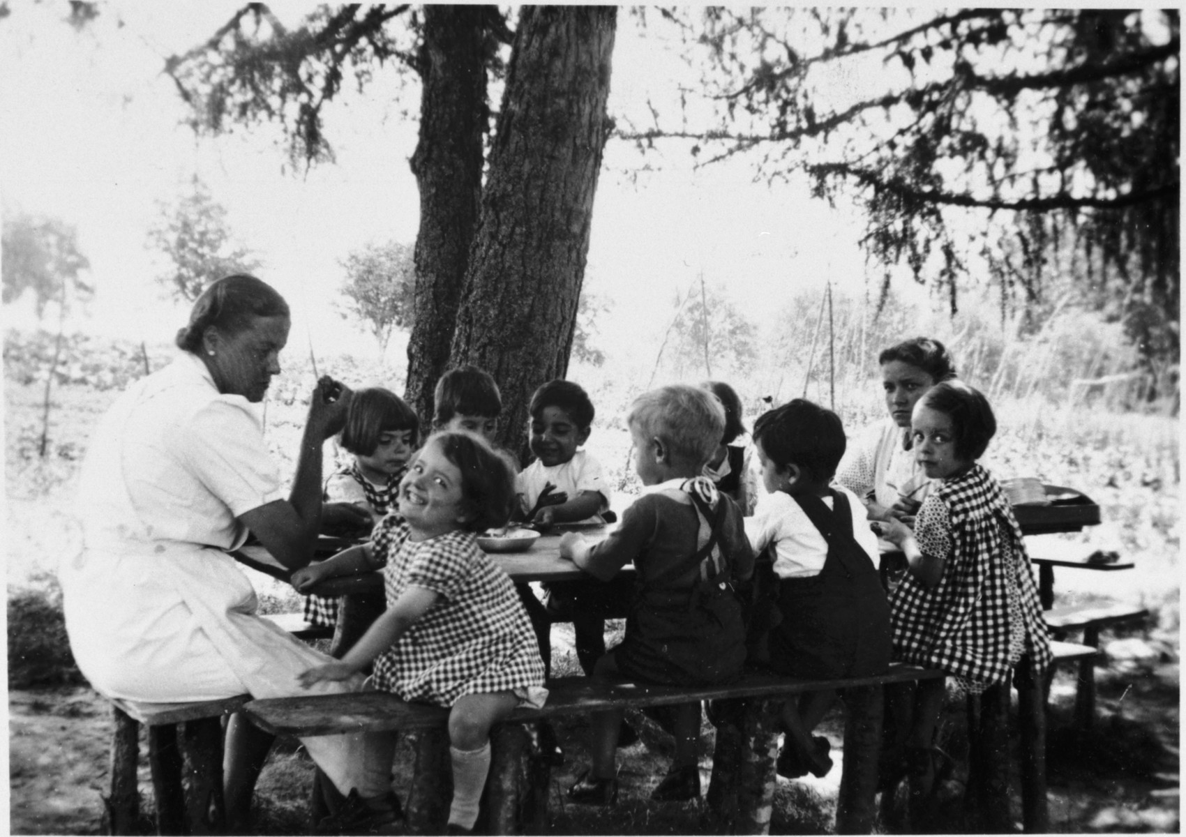 Young children gather around a picnic table in the Chateau des Avenieres children's home in Cruseiles.  Among those pictured is the teacher, Aloisia Schwarzschild.