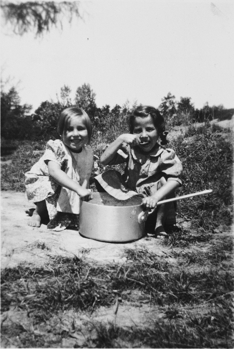 Two little girls eat from a large pot in the Chateau des Avenieres children's home in Cruseiles.