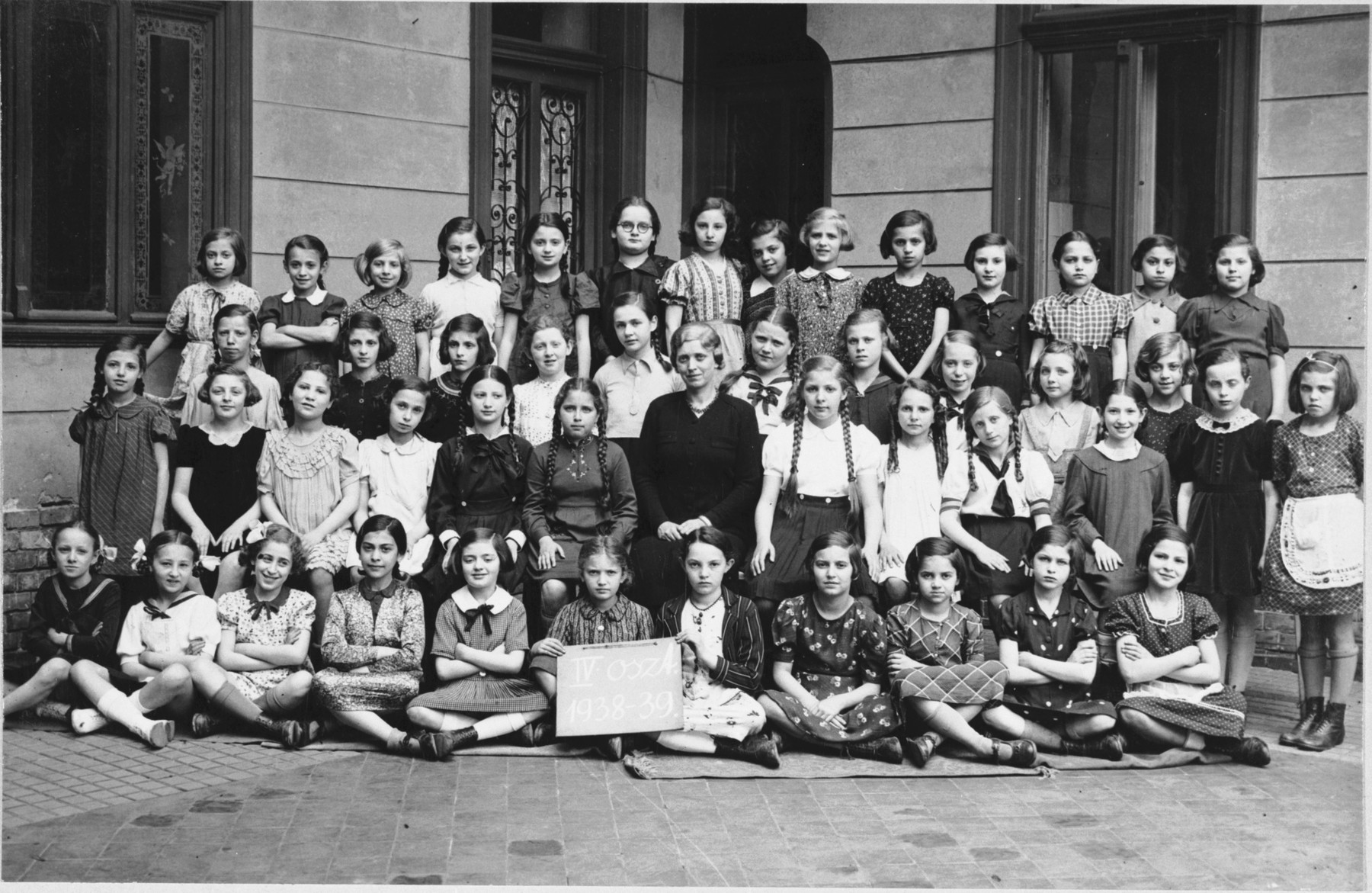 Group portrait of an elementary school class of an Orthodox Jewish school in Budapest which met in the Kazinczy Street Synagogue.  Among those pictured is Anna Roz (top row, fourth from the right.)