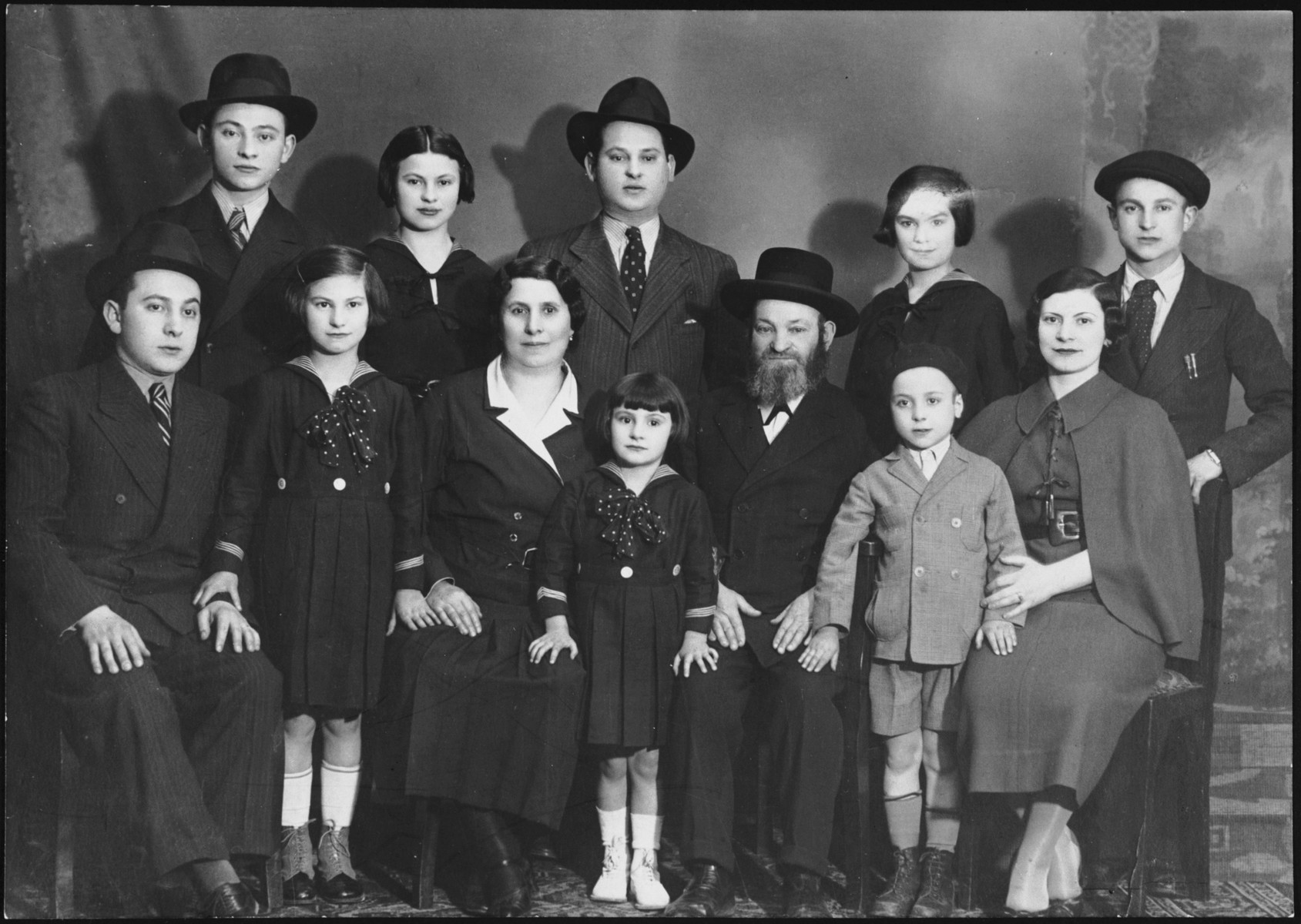 Prewar portrait of a large Hungarian Jewish family in Budapest.  Pictured are the Roz family.  Seated are Marton, Erzsi, Hermina, Anna, Herman, Andor and Szeren Roz.  Standing are Jeno, Iren, Armin, Ilona and Vilmos Roz.