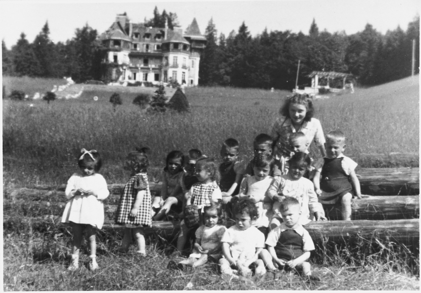 A half-Jewish teenage girl who survived the war in hiding poses with a group of the youngest children in the Chateau des Avenieres children's home in Cruseiles.  Pictured in the back right is Margot Schwarzschild.