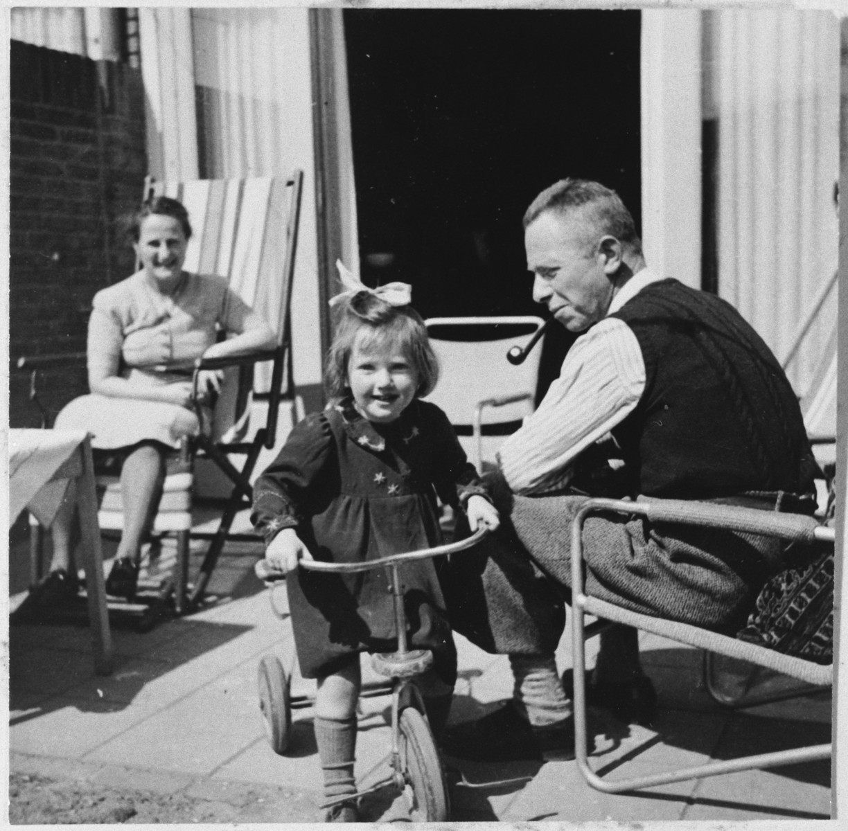 A Jewish family relaxes on their porch in Eindhoven shortly before they had to go into hiding.  Miep van Engel is riding her tricycle in the foreground.  Her father Bernard van Engel is on the right.  Ro Bierman is seated in the back.