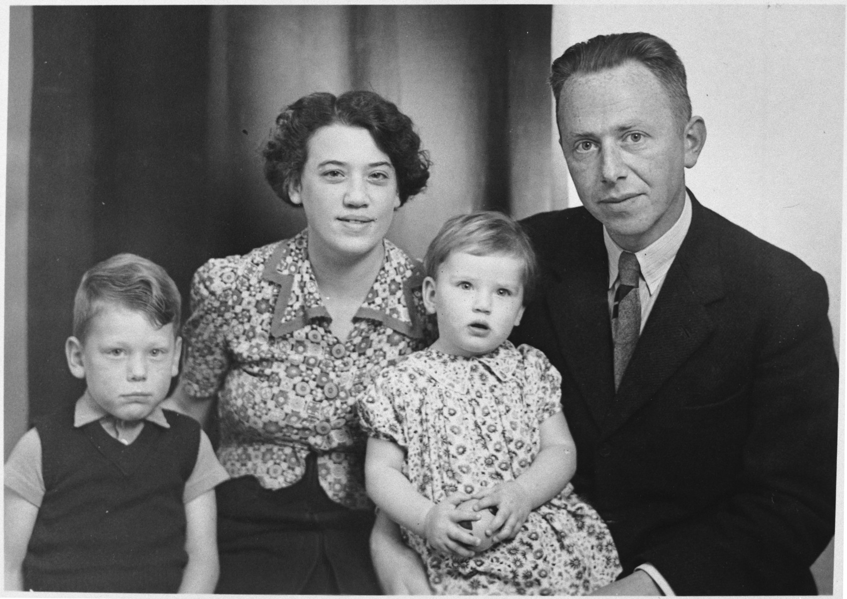 Studio portrait of a Dutch Jewish family taken either right before or right after the German invasion of the Netherlands.  Pictured are Max, mother, Miep and Bernard van Engel.