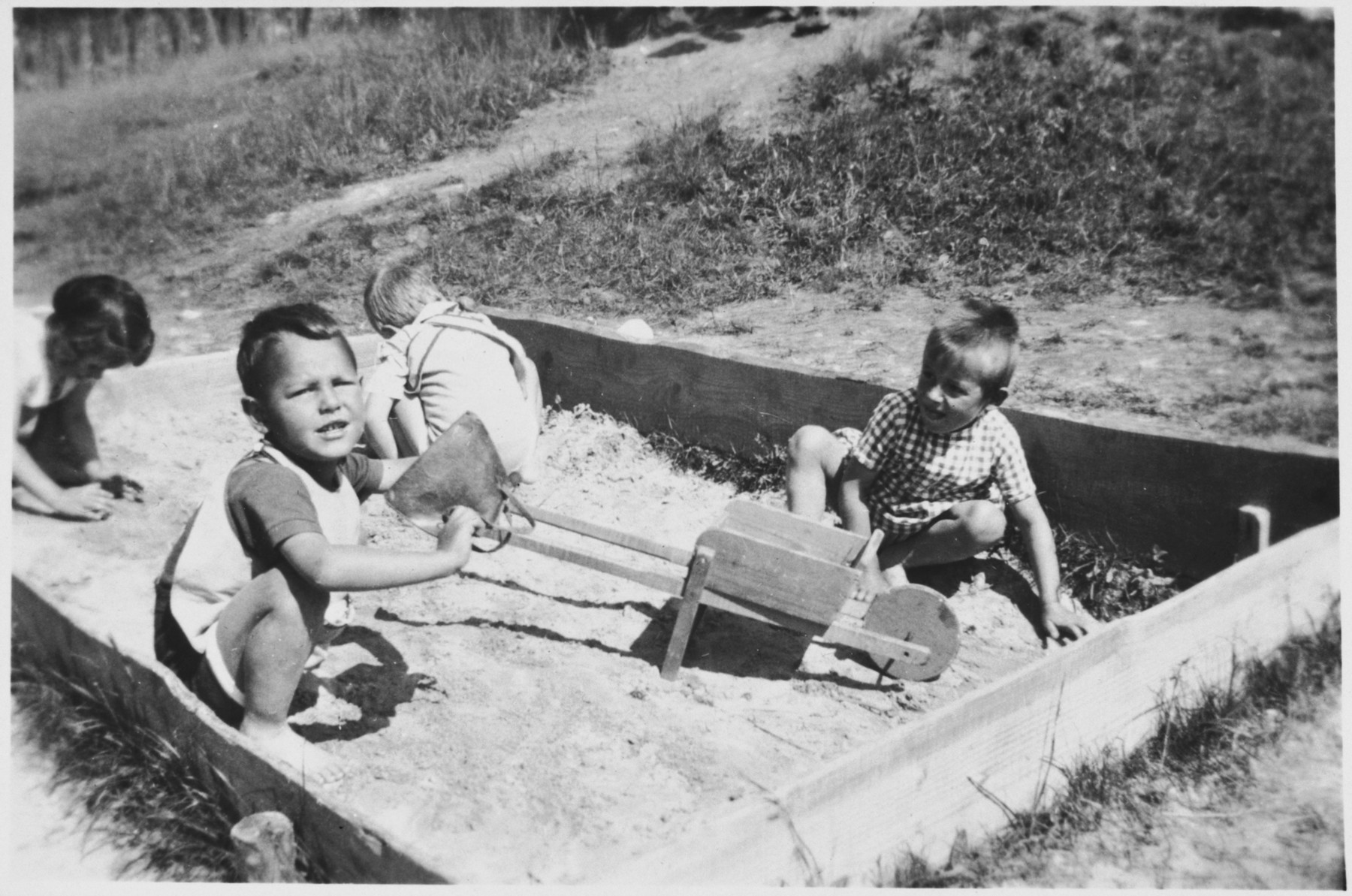 Three little boys play in the sandbox outside the Chateau des Avenieres children's home in Cruseiles.