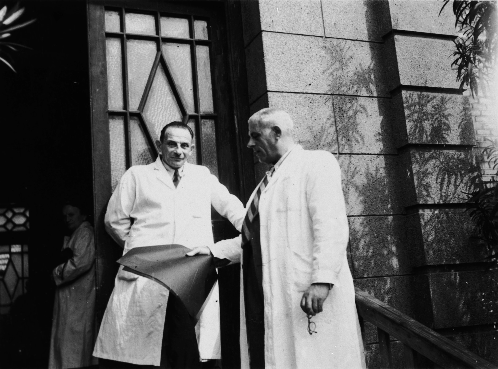 Two physicians stand outside the hospital in Shanghai.  The doctor holding his glasses in his hand is Dr. Hugo Levinsohn.  He was the chief medical officer of the American Jewish Joint Distribution Committee.