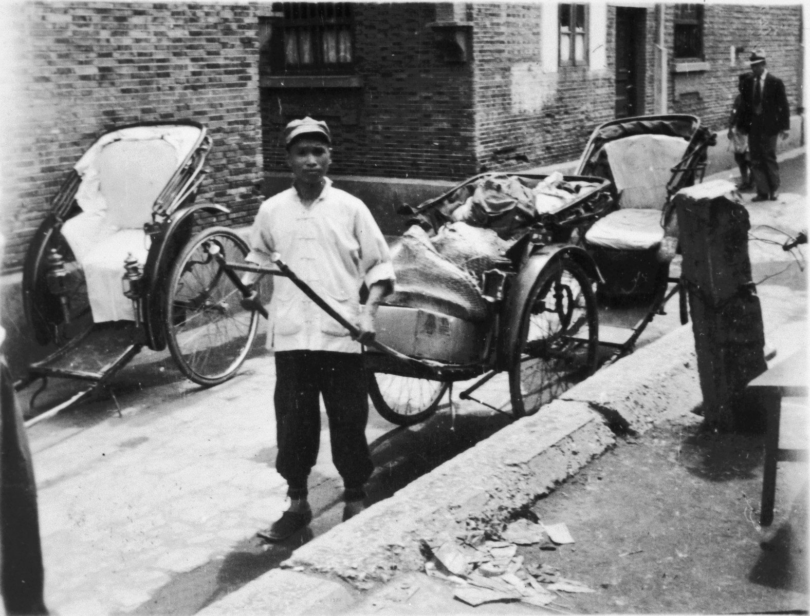 A Chinese man pulls a hand cart filled with bundles down a street in Shanghai.