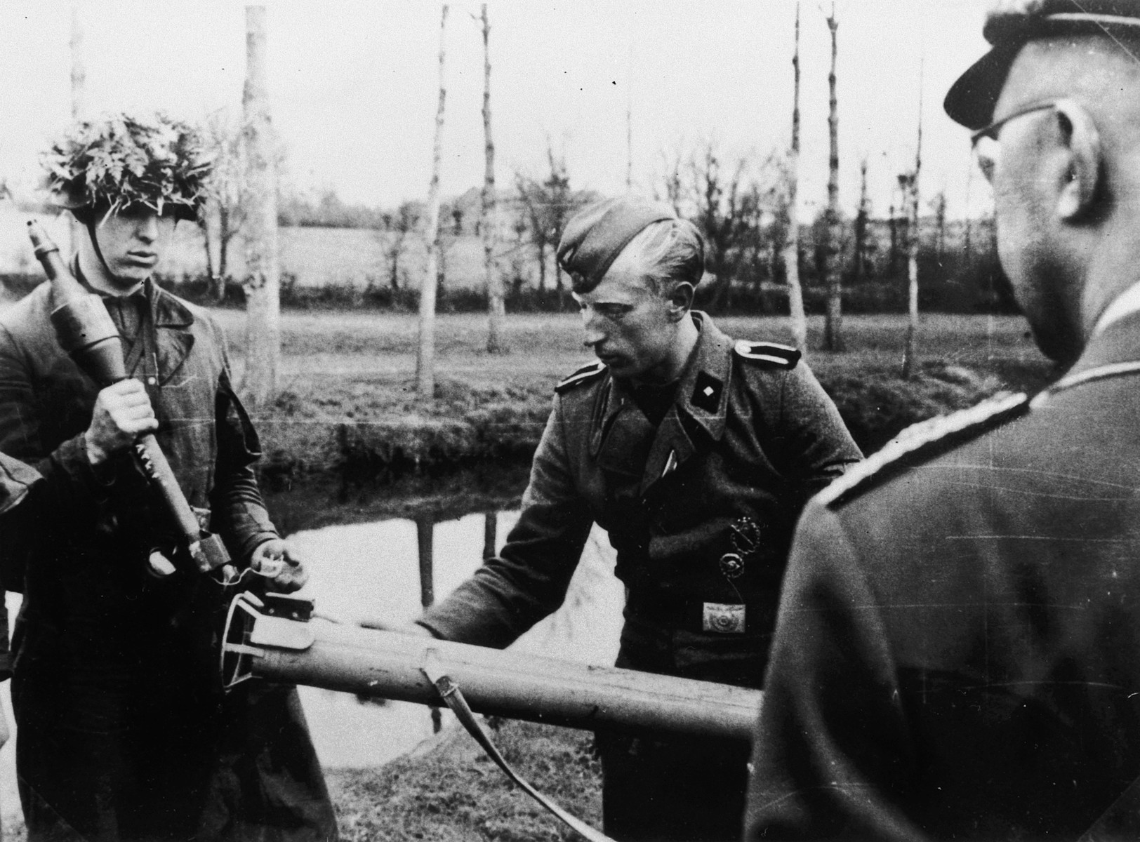 Reichsfuehrer Heinrich Himmler observes two German soldiers, one in a camoulflaged helmut, loading a mortar in an unidentified location.  According to a researcher Himmler is talking with unknown soldiers of Gatz von Berlichingen. The photo was taken in Thouars on April 10, 1944 during the formation of the SS-Division Gatz von Berlichingen.  The researcher received this information from Himmlers adjutant Werner Grothmann who Iidentified this and several other photos from the same time.