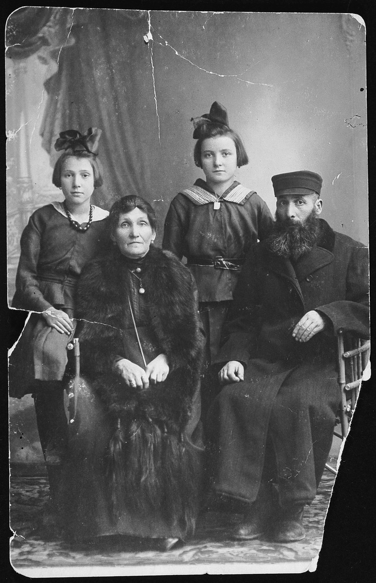 Studio portrait of a religious Jewish family in Kielce.  Pictured are Udla and Welwal Szkolnick and two daughters, Feigla and Shendla.