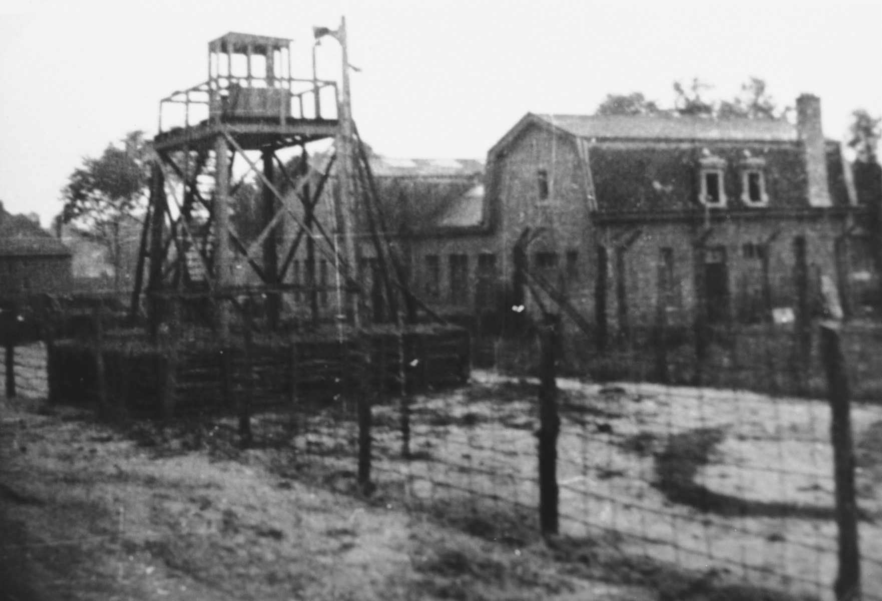 View of the watch tower and barbed wire fence surrounding the ...