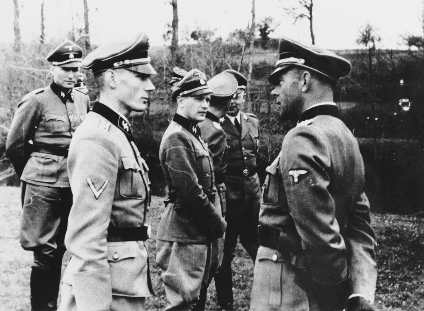 German SS officers confer in an unidentified location.  According to a reacher Werner Ostendorff is at the far right. The SS-Obergruppenfuehrer Carl Oberg is in the back, The photo was taken in Thouars on April 10, 1944. This during the formation of the SS-Division GÃtz von Berlichingen. The researchers's information came from Himmlers adjutant Werner Grothmann who Iidentified this and several other photos from the same time.