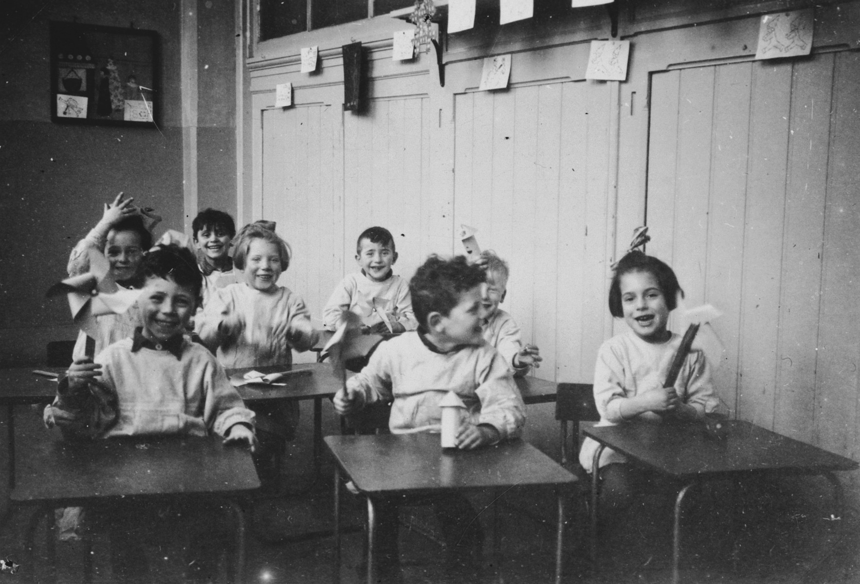 Young Dutch-Jewish children brought from the creche to a children's home by the Dutch underground sit at their desks.