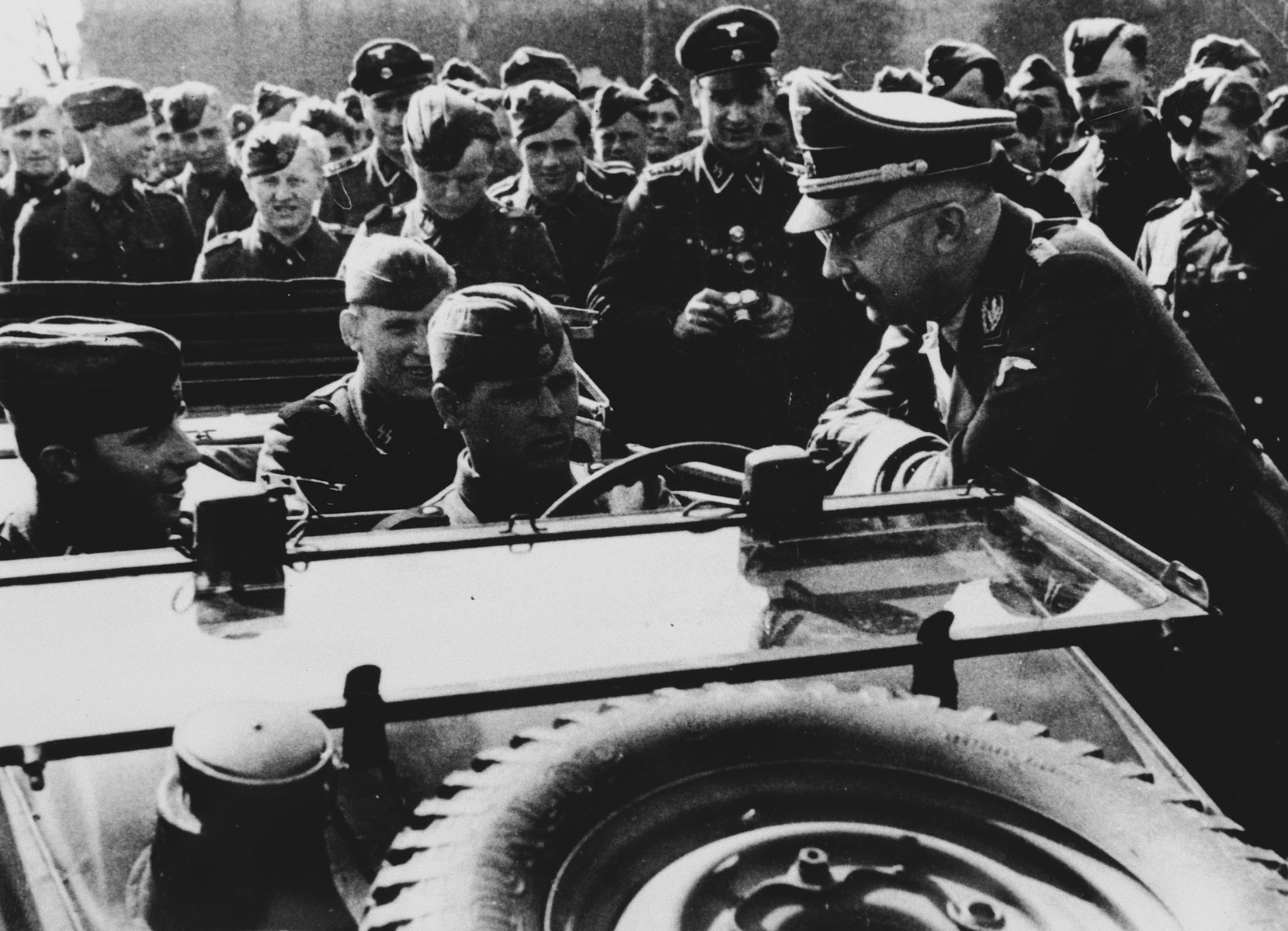 Reichsfuehrer Heinrich Himmler talks with German troops seated in an open military vehicle in an unidentified location.  According to a researcher Himmler is talking with unknown soldiers of Gatz von Berlichingen. The photo was taken in Thouars on April 10, 1944 during the formation of the SS-Division Gatz von Berlichingen.  The researcher received this information from Himmlers adjutant Werner Grothmann who Iidentified this and several other photos from the same time.