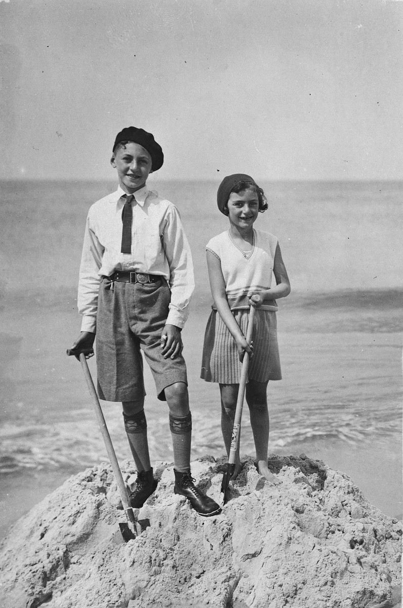 Two Jewish siblings dig in the sand at the beach in The Netherlands.  Pictured are Joachim and Hilde Jacobsthal.