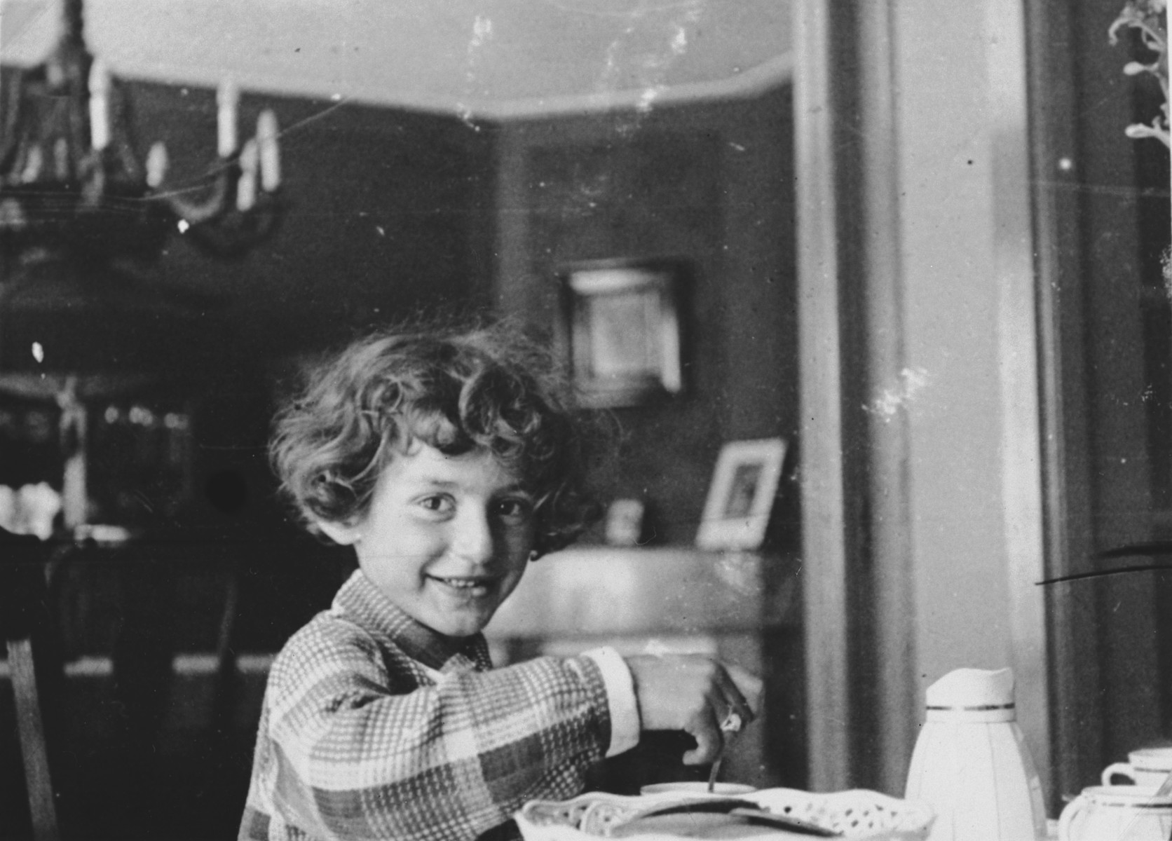Close-up of a  Jewish girl sitting at a table in her dining room in Amsterdam.  Pictured is Hilde Jacobsthal.