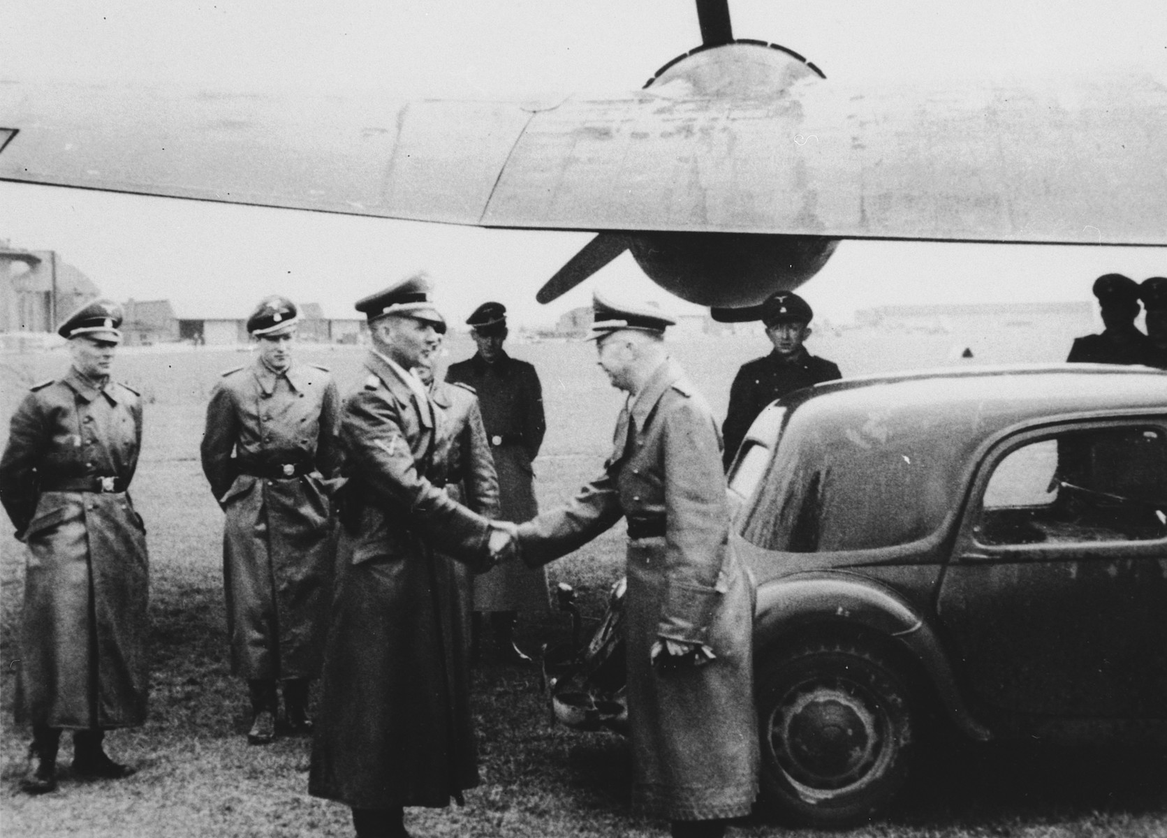 Reichsfuehrer Heinrich Himmler greets an unidentified officer beneath the wing of a military airplane.  Also pictured is SS-Sturmbannfuehrer Werner Grothmann, on the far left.