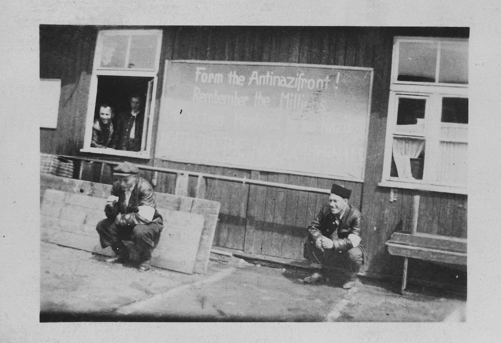 Two survivors sit outside a barrack beneath a bulletin board in the Buchenwald concentration camp.