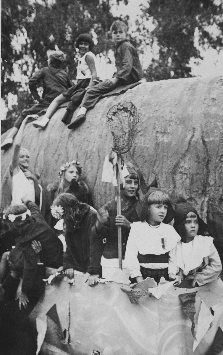"Children, some of whom are in costume, from the Berlin housing development known as Uncle Toms' Cabin climb on a giant fish during an annual parade.  Part of the area was called ""Fischtalgrund"" (Valley of the Fish).  Seated on top of the fish, second from the left is Irene Spicker."