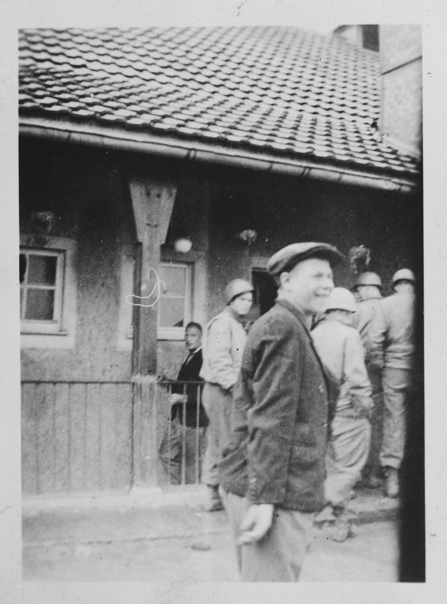 American soldiers enter a barrack in the Buchenwald concentration camp while a survivor smiles in the foreground.