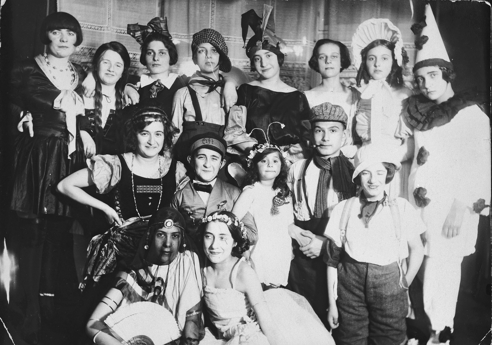 A large group of German and Jewish friends pose together during a costume party.  Pictured in the center is Irene Spicker next to her older brother Werner.