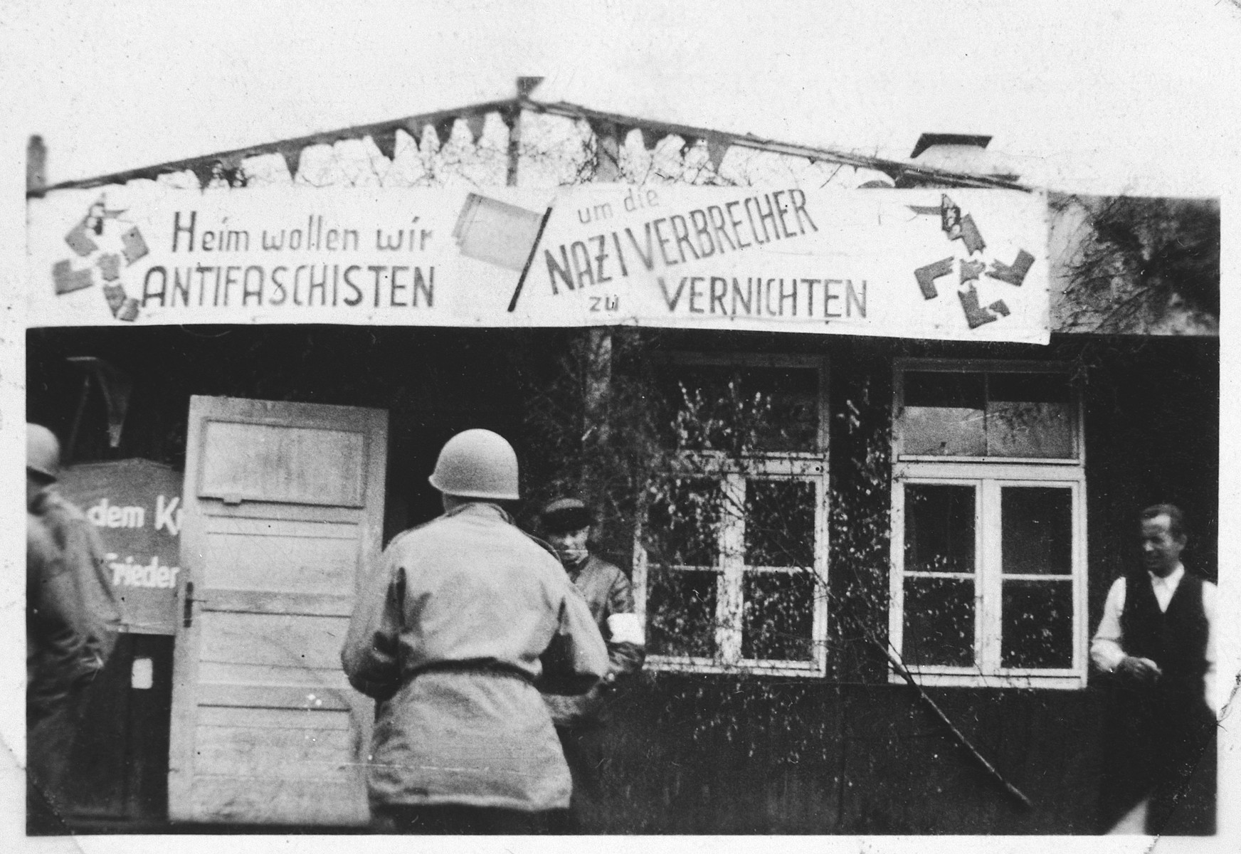 An American serviceman looks at an anti-Nazi banner hanging outside a barrack in the Buchenwald concentration camp.