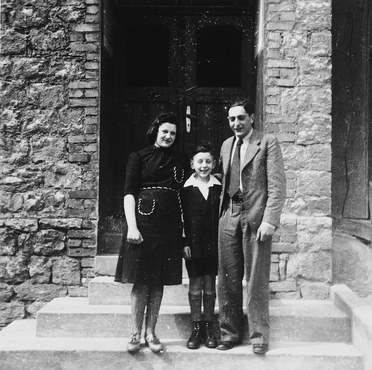 A German-Jewish boy poses outside his home in Rimbeck, Germany with his parents on the occasion of his bar mitzvah.  Pictured are Mathilde, Ludwig and Siegfried Fischel.  Half a year later the family was deported to Riga.