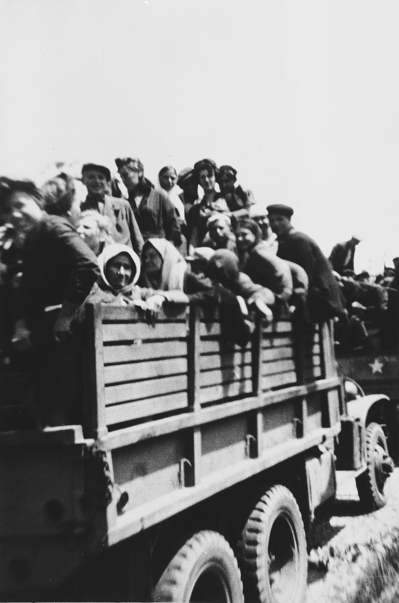 Hungarian-Jewish survivors of a concentration camp near Homberg, Germany depart the camp on board a convoy of trucks.  These women were liberated from soldiers from the 6th Armored Division.