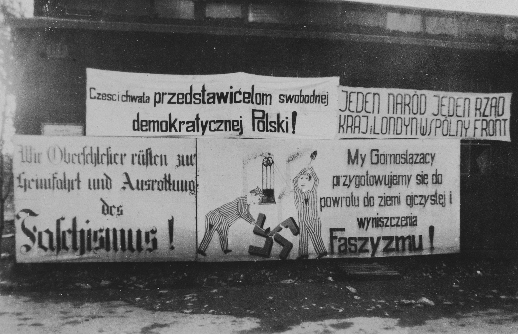 Anti-Nazi posters in German and Polish drawn by freed prisoners hang outside a barrack of the Buchenwald concentration camp.