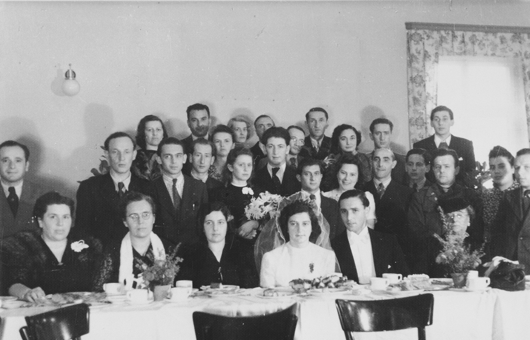 Group portrait of friends and relatives who are celebrating the marriage of Lily Fischel and Leon Pancis in the Bad Wildungen displaced persons' camp.  The bride and groom met each other in concentration camp.  Ludwig Fischel, a cousin of the bride, is pictured on the right with a flower on his suit.