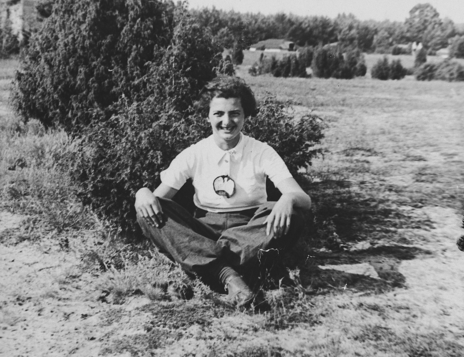 A Jewish teenage girl poses next to a shrub in the Polish countryside.  Pictured is Janina Bussgang.