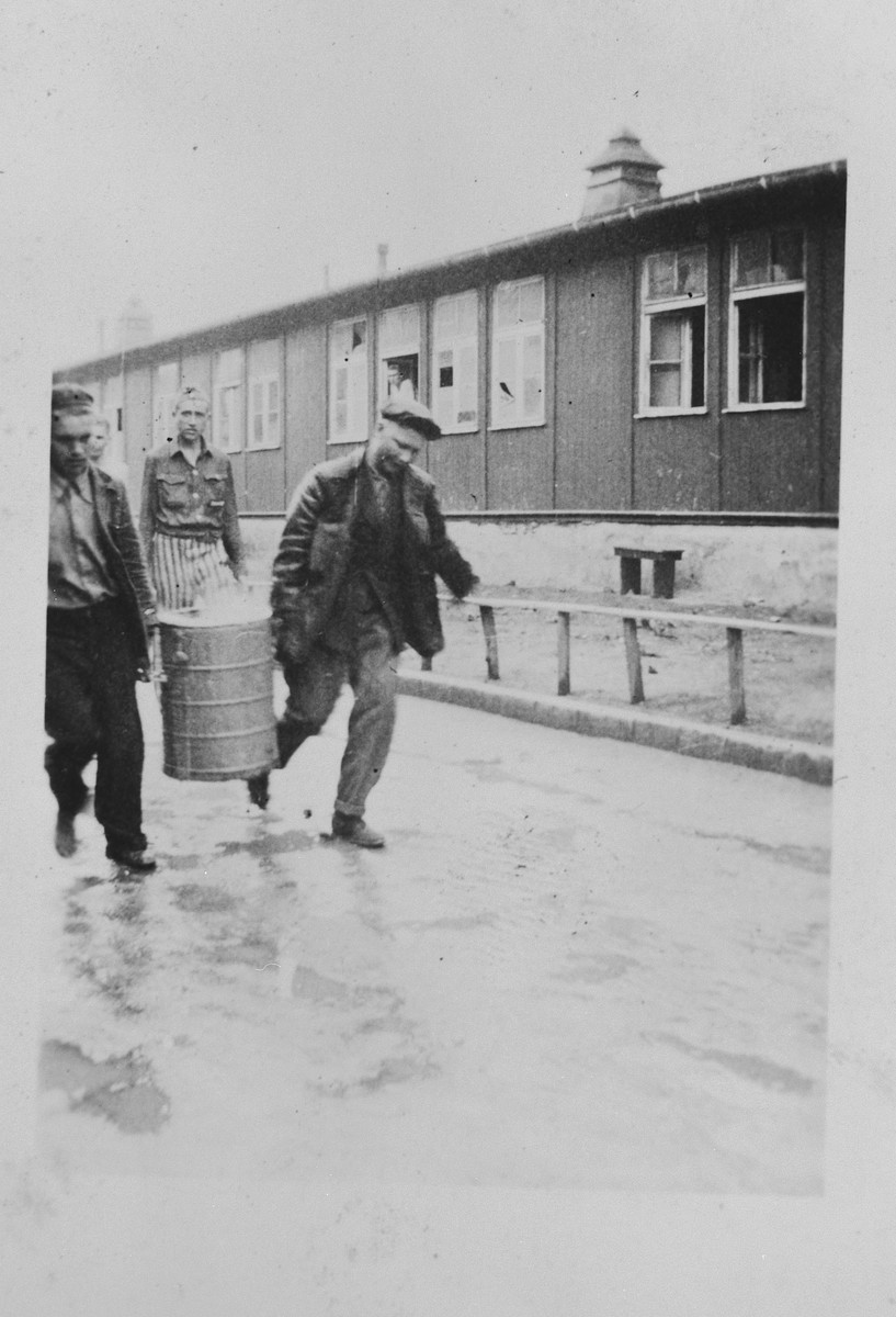 Two survivors walk past a barrack in the Buchenwald concentration camp carrying a large cannister [probably containing soup].