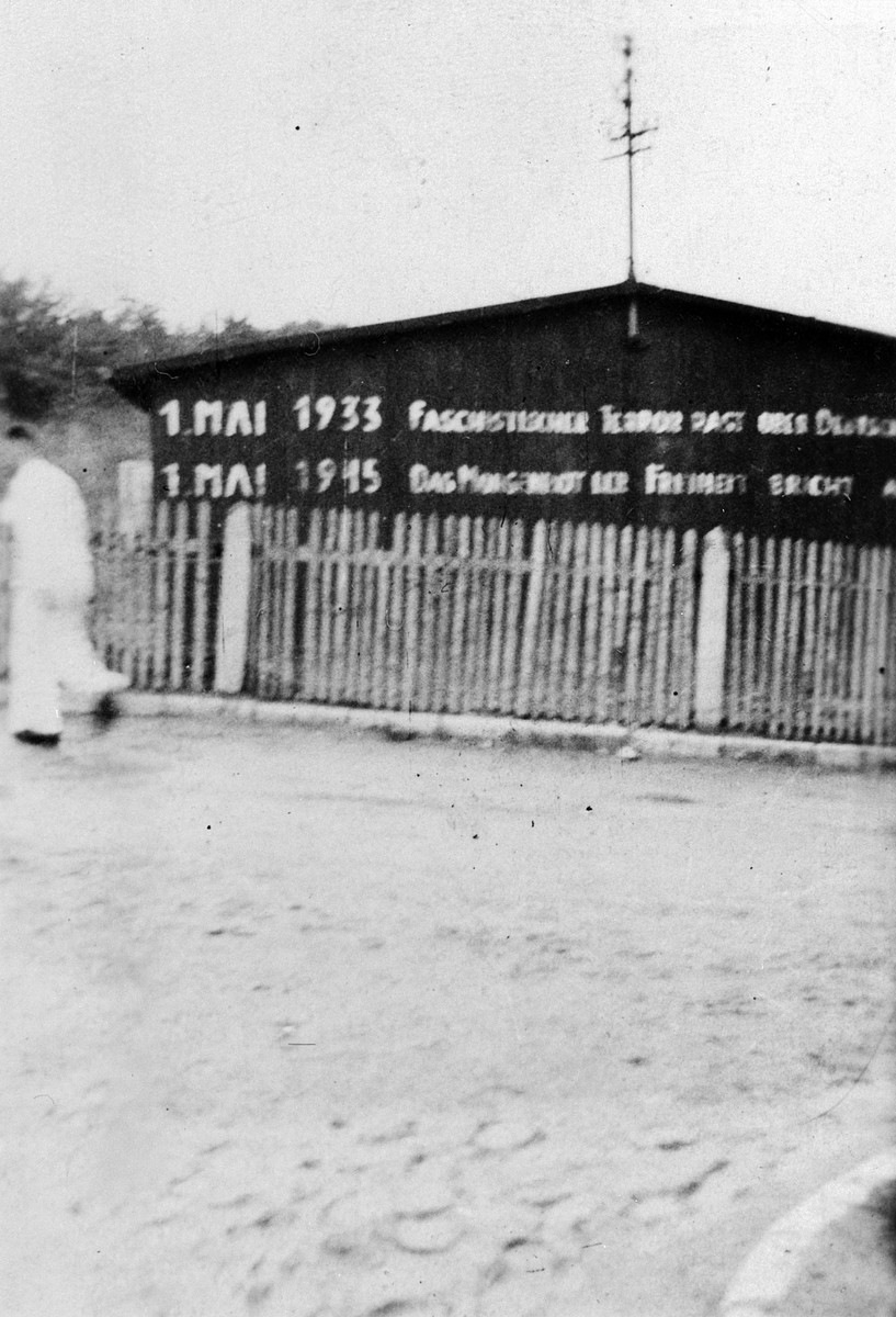 A survivor walks past a sign on the exterior of a barrack in the Buchenwald concentration camp describing the significance of May 1 in both the years 1933 and 1945.