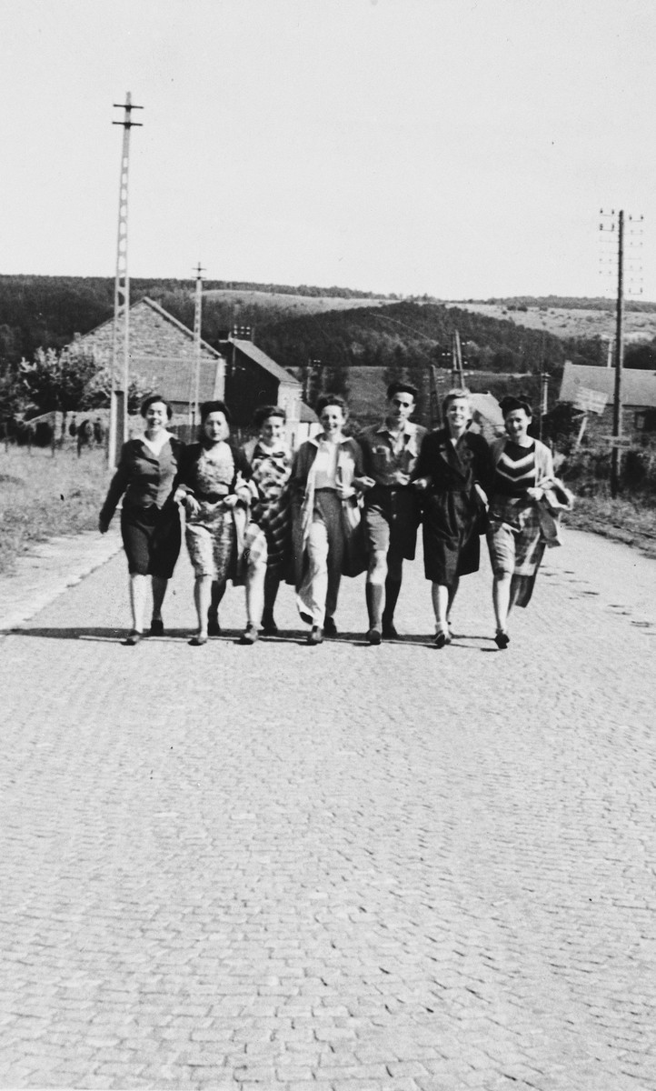 A group of friends walks arm-in-arm down a street in the Ardennes.  Included in the group is Irene Spicker (left), a German-Jewish refugee.