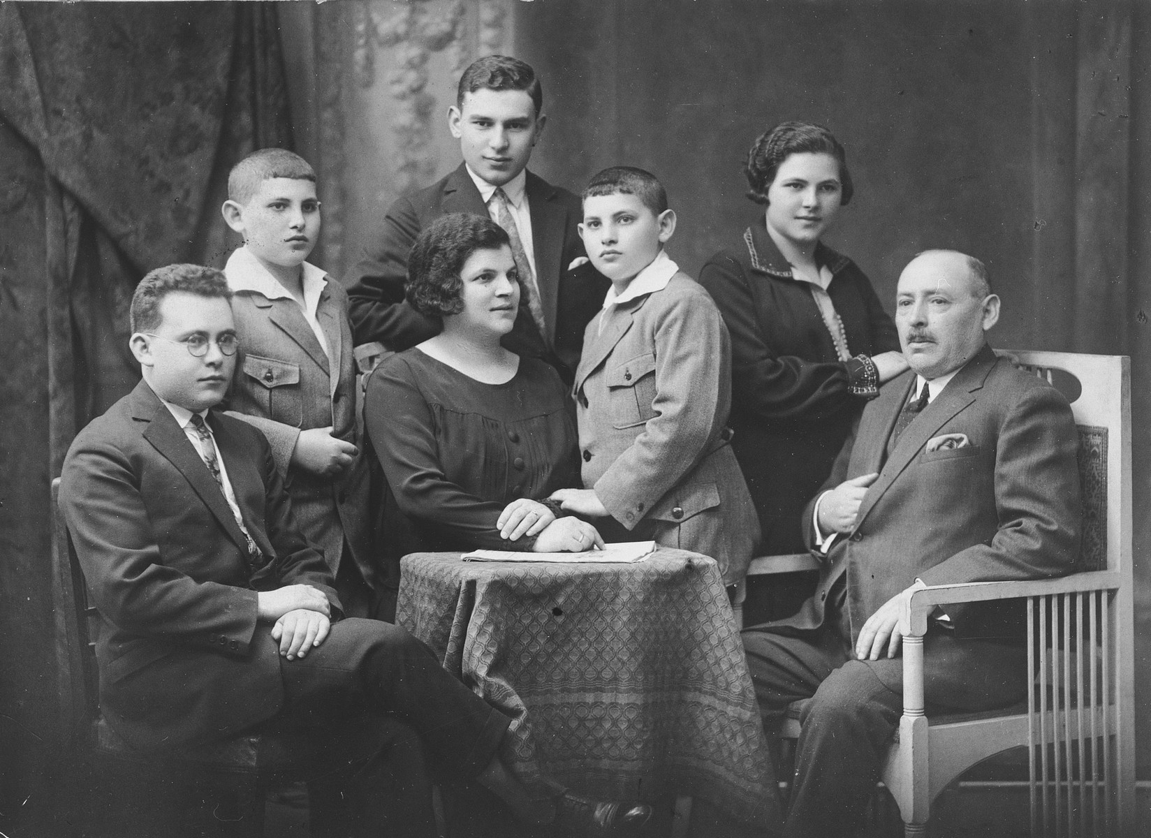 Studio portrait of a Jewish family from Sosnowiec Poland.  From left to right are Asher, Itzchak, Basha, Jacob, Solomon, Felicia and Bernard Grajcer.