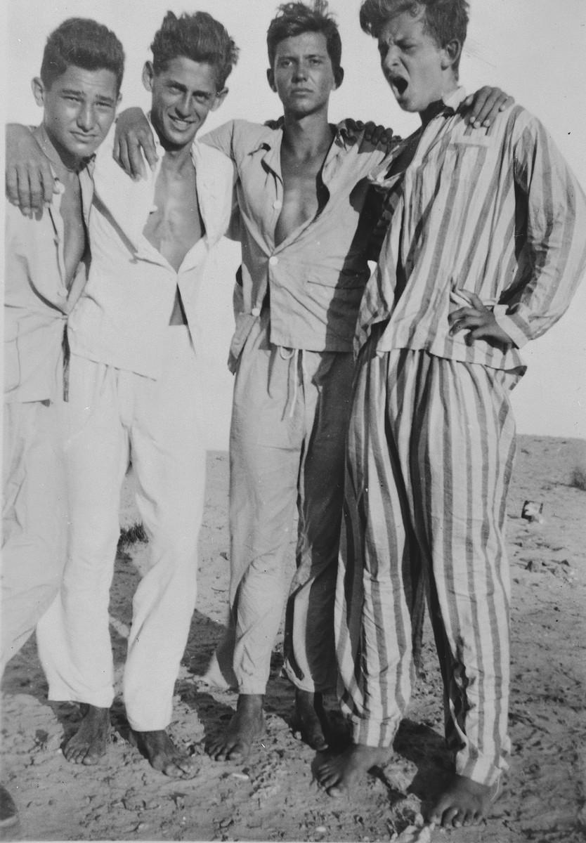 Group portrait of four high school friends from the Polish high school in Tel Aviv standing on the beach in Bat Yam.  Pictured are Julian Bussgang, Karol Zehnwirt, Adam Baar and Jurek Swida.