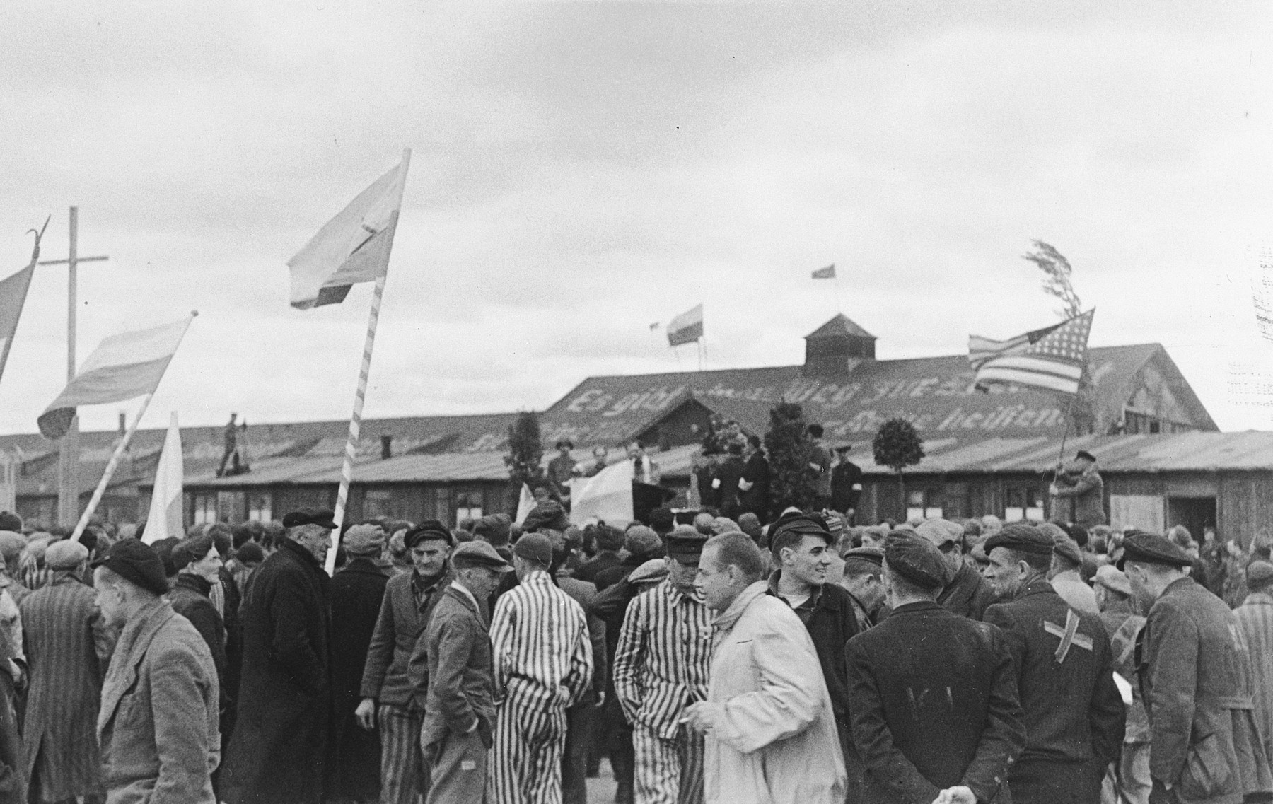 Survivors waving flags of different nationalities flock to an outdoor Jewish memorial service in the liberated Dachau concentration camp.