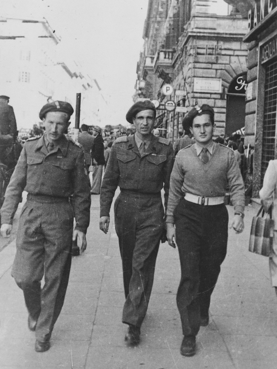 Three members of the Anders Army walk down a street probably in Italy.  Pictured on the right is Lance Corporal Julian Bussgang.  On the left is Andrzej Sienkiewicz. In the center is Zbigniew A. Konczacki who after the war emigrated to South Africa and then moved to Halifax, Canada, where he taught economics of tropical Africa