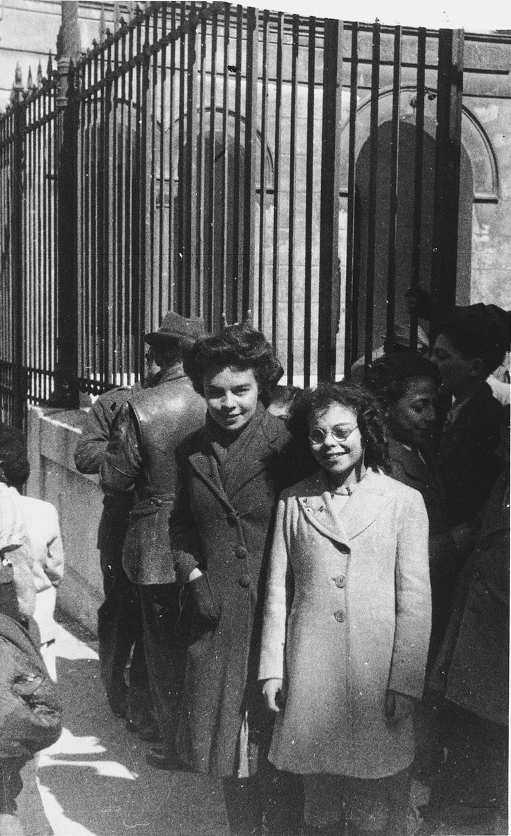 Two Jewish girls stand outside the entrance to the synagogue in Marseilles where an American Jewish chaplain is organizing Passover religious services.  The uncle of one of the girls was a general with the Free French Forces.