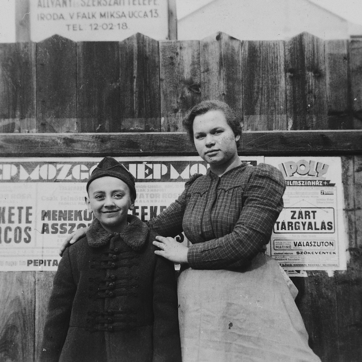 A young Jewish boy poses with his Hungarian nanny in front of a poster tacked on a wooden fence in Budapest.  Pictured is Ivan Pal.